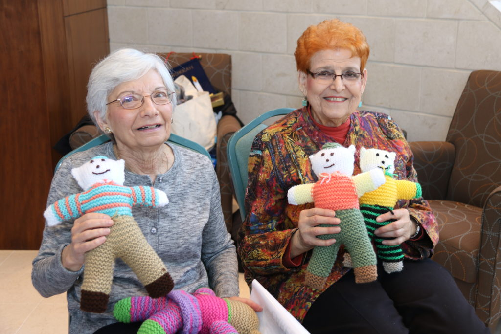 women holding knitted bears